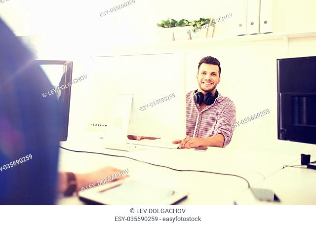 business, startup, education, technology and people concept - happy creative man or student with headphones and computer at office