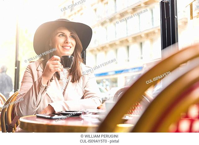 Stylish young woman drinking coffee in cafe, Paris, France