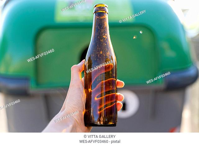 Close-up of man holding bottle for recycling