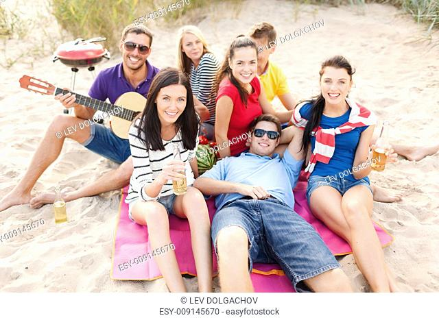 summer holidays, vacation, music, happy people concept - group of happy friends having picnic and playing guitar on beach