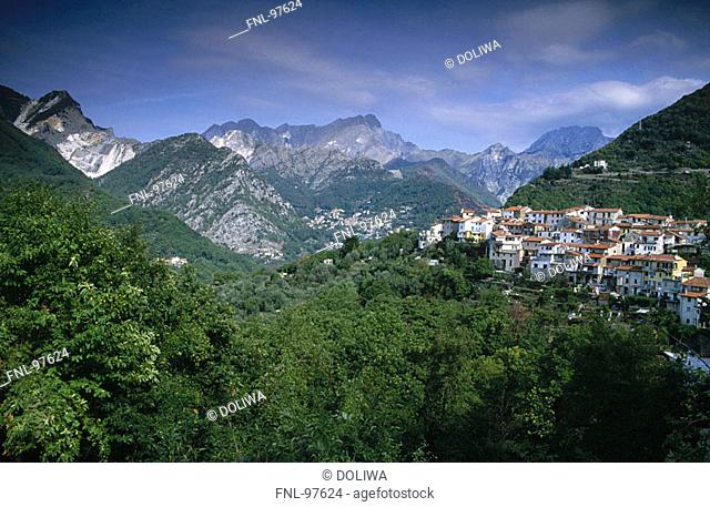 Village in a valley with mountains in the background, Versilia, Tuscany, Italy