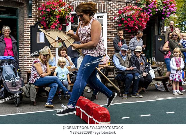 Local People 'Showjumping' With A Toy Horse At The Annual South Street Sports Day and Dog Show, Lewes, East Sussex, UK
