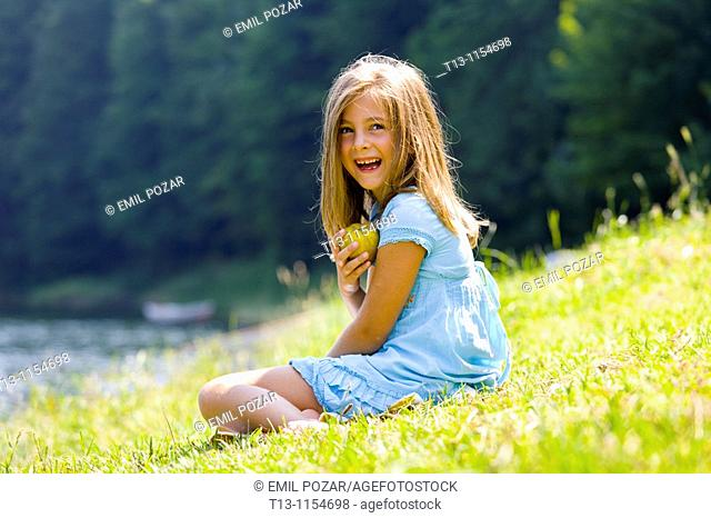 Six year old girl is laughing and holding a pear