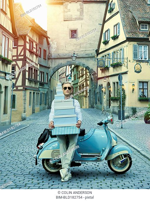 Caucasian man with gift boxes on vintage scooter in village