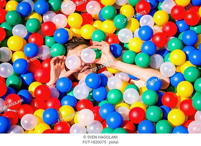 Playful young man laying in multicolor ball pool