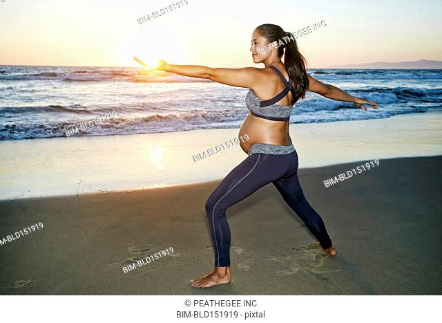 Pregnant Hispanic woman practicing yoga on beach