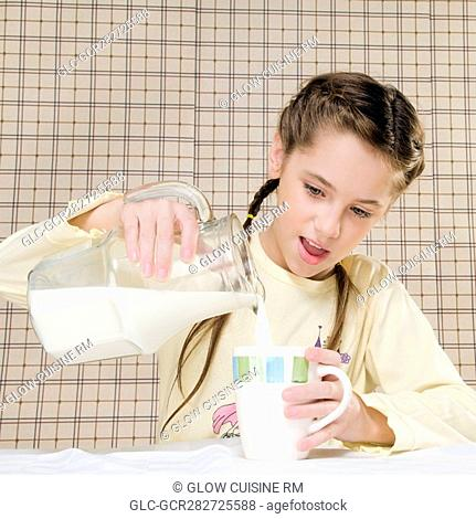 Close-up of a girl pouring milk in a cup