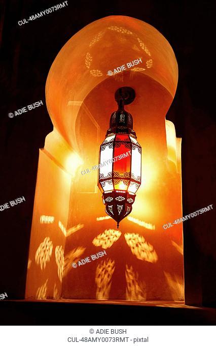 Ornate metal lantern lit up at night