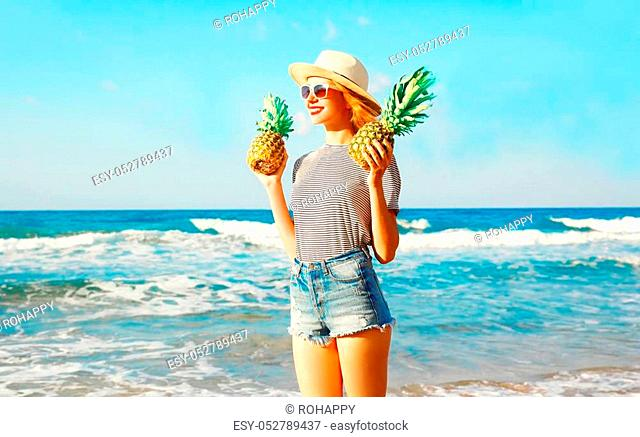 Happy smiling woman holds a two pineapples over sea background on summer day