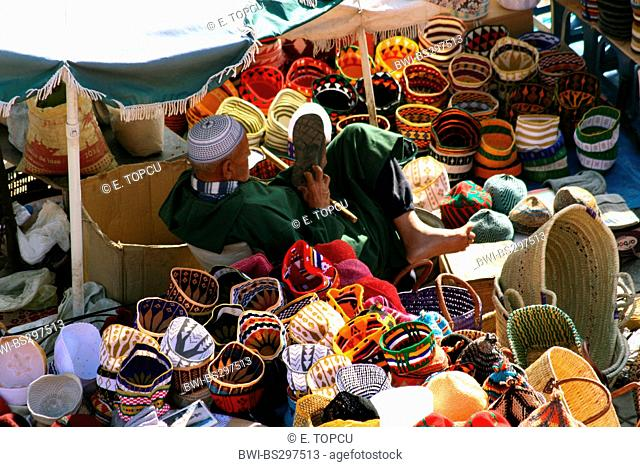 marketer sitting between traditional handwork, baskets and headpieces, Morocco, Marrakesh