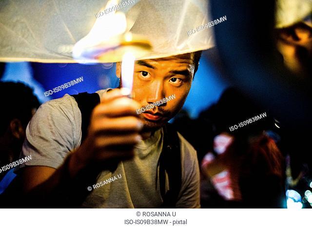 Young man lighting paper lantern for Loy Krathong Paper Lantern Festival in Chiang Mai, Thailand