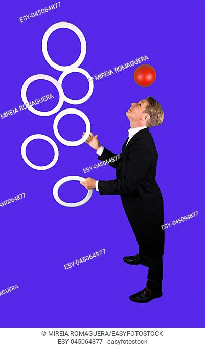 Elegant and happy juggler with five juggling clubs and one ball