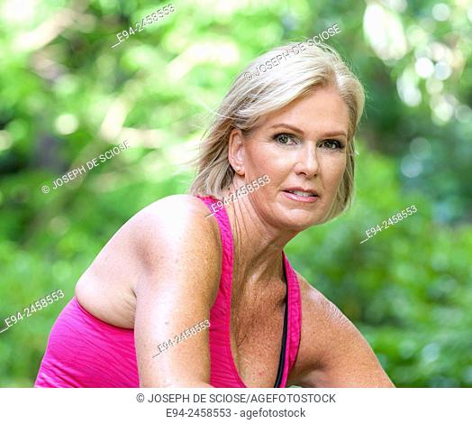 56 year old blond woman smiling at the camera, outdoors