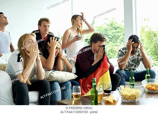 German football fans watching football match at home