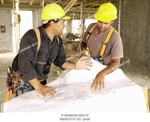 Hispanic workers looking at blueprints on construction site