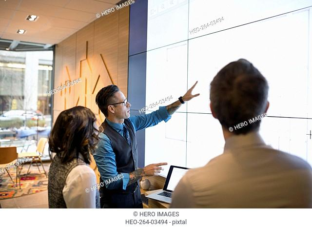 Architects discussing blueprints on projection screen conference room
