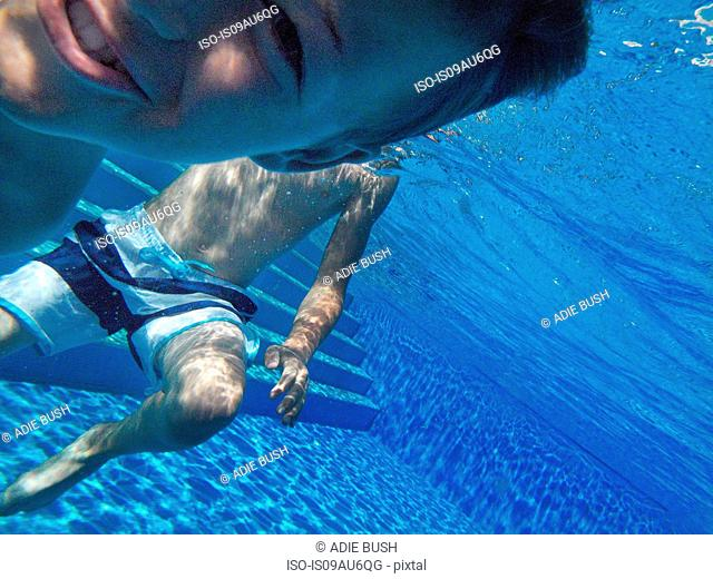 Close up underwater portrait of boy in swimming pool