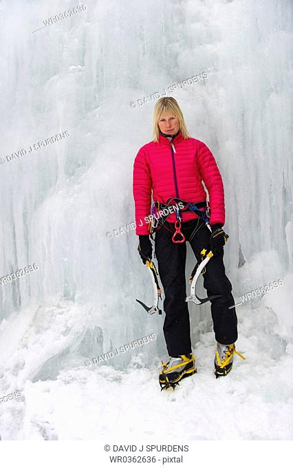 Female Ice Climber on icy waterfall looks at camera