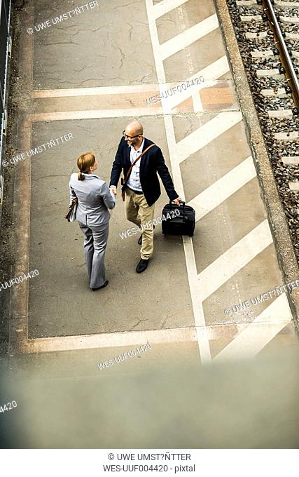 Businessman and businesswoman shaking hands on railway platform