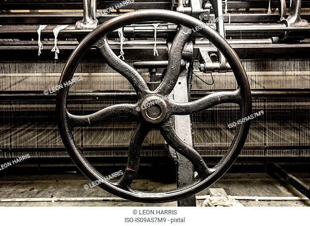 Iron wheel on old weaving machine in textile mill