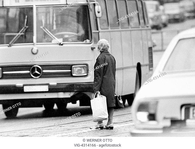 DEUTSCHLAND, BOTTROP, 08.07.1972, Seventies, black and white photo, people, older woman with shopping bags stands in the middle of a traffic road and tries to...