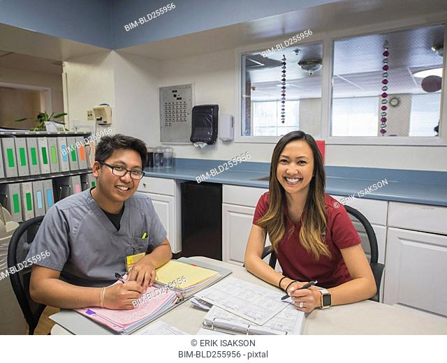 Portrait of smiling nurses writing in binders in hospital