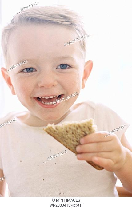 Portrait of a smiling young boy eating a sandwich