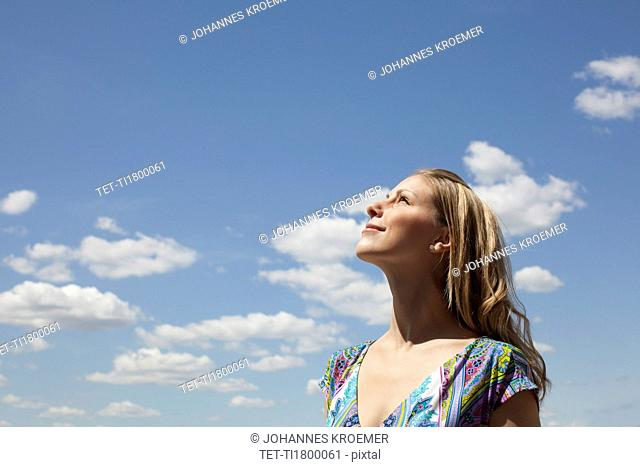 Young woman smiling against cloudy sky