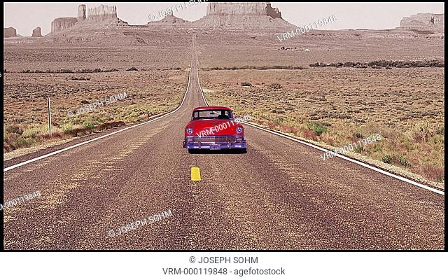 1956 Red Chevy drives straight down Monument Valley towards camera, Utah, Route 163