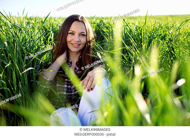 Portrait of smiling young woman sitting in a field