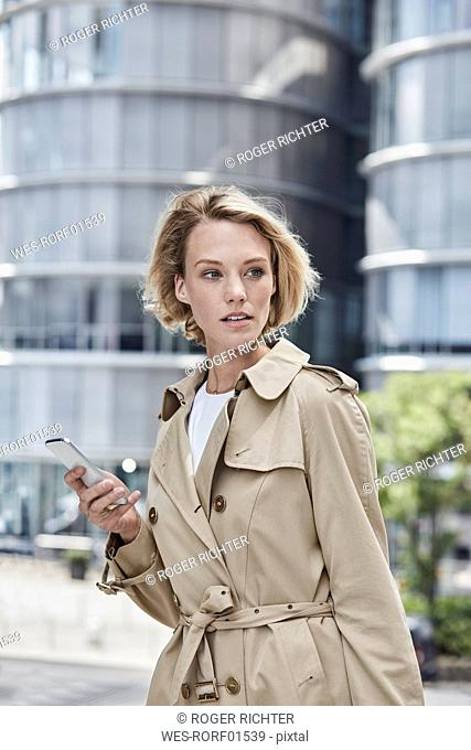 Germany, Duesseldorf, portrait of blond young businesswoman with smartphone wearing beige trenchcoat