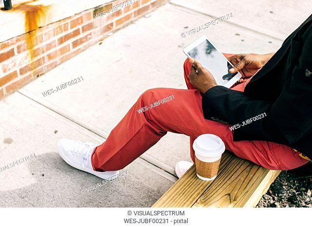 Man sitting in the street, using digital tablet, drinking coffee