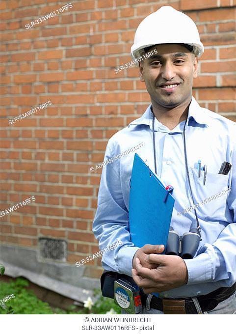 Businessman in hard hat carrying folder