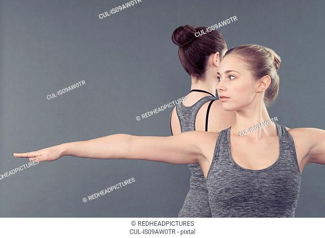 Young women practising yoga, grey background