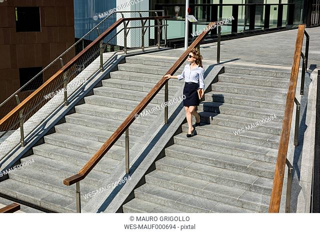 Businesswomanwalking downstairs outdoors