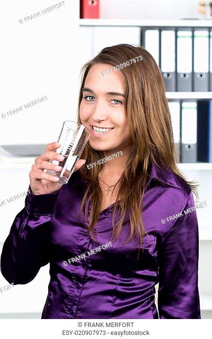 Frau trinkt Wasser aus einem Glas