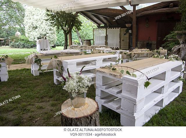 Garden center decorated for wedding party with wood benches in Jai Alai restaurant, Urrestilla, Basque Country, Spain