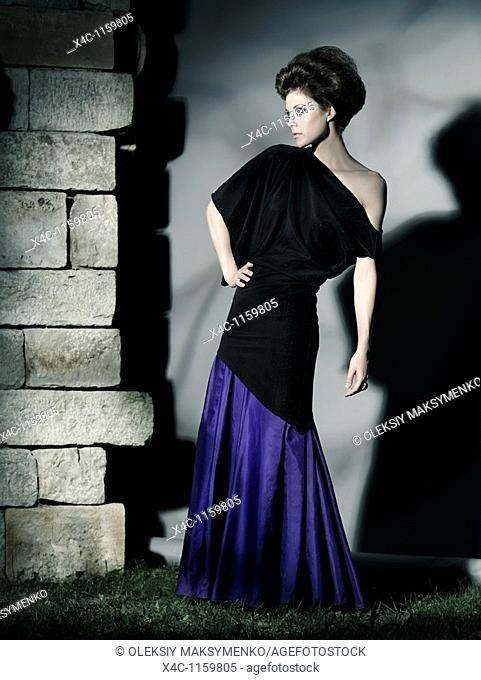 High fashion photo of a beautiful woman wearing elegant long dress