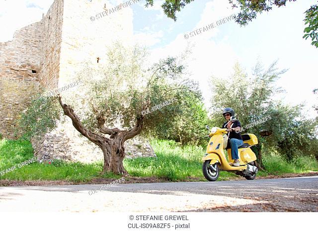 Woman on scooter riding around corner
