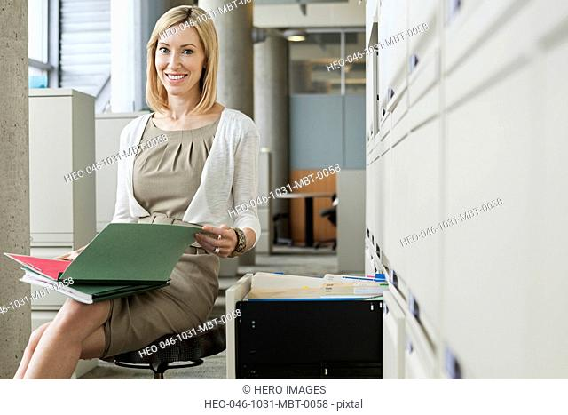 Businesswoman with file folders at filing cabinet in office