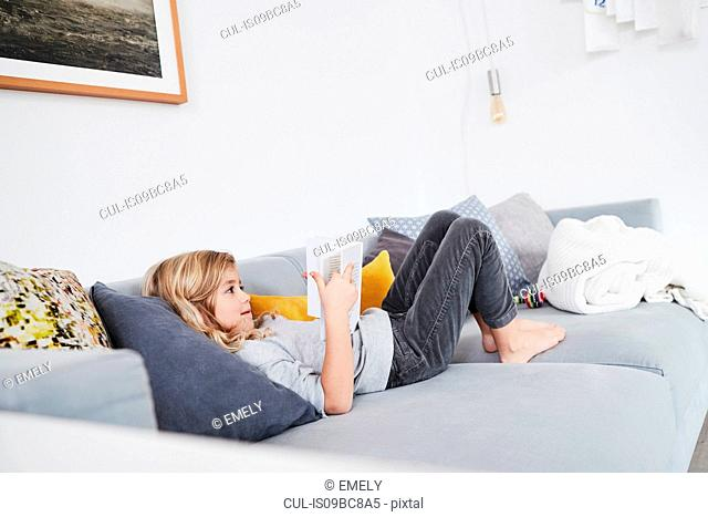 Young girl lying on sofa, reading book