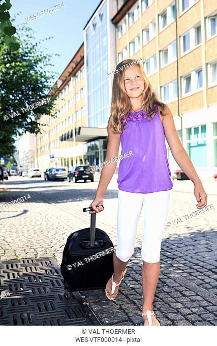 Germany, Girl holding luggage