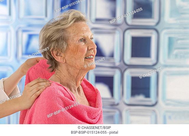 Nurse helping a senior woman to wash
