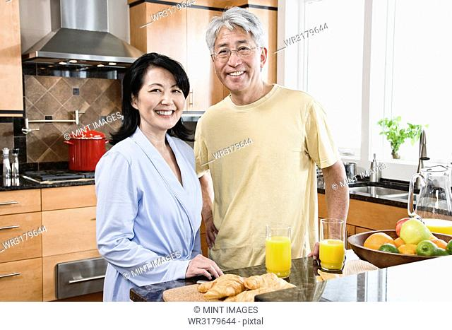 Asian man and woman in their new kitchen for breakfast