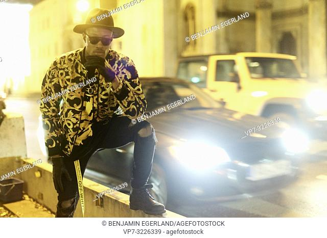 confident blogger man at city street at night, wearing stylish outfit, blurred car, traffic, cool attitude, at Ludwigstraße in Munich, Germany