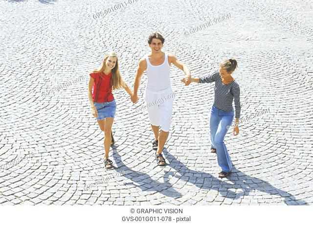 Portrait of a young man and two young women walking holding hands
