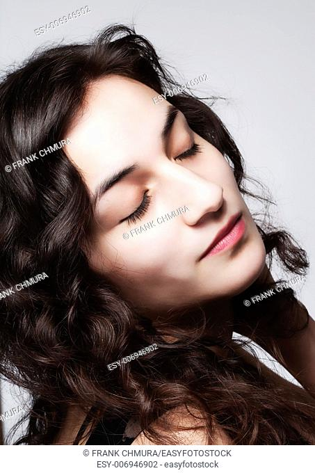 Young Beautiful Woman with Long Brown Hair and Closed Eyes