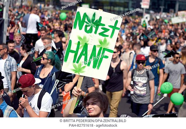 A participant of the 20th Hemp Parade holding up a sign reading 'Nutzt Hanf' (lit. 'Use Hemp') in Berlin, Germany, 13 August 2016