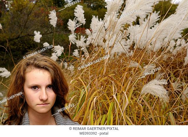 Young girl standing by a river in the Fall with tall wild white plumed Pampas Grass