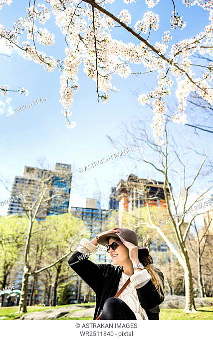 Young woman holding hat and sitting against buildings at Central Park